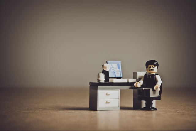 Lego Man Sitting at Computer Looking Worried